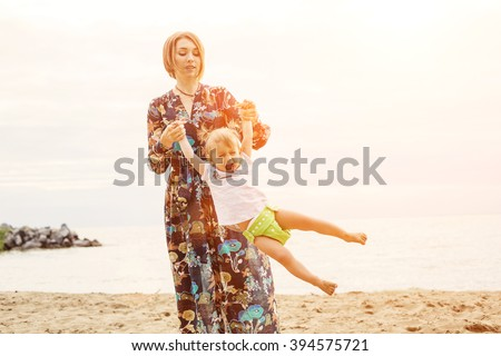 Mother and baby daughter playing on the beach. Relaxing, fun and family time  - stock photo