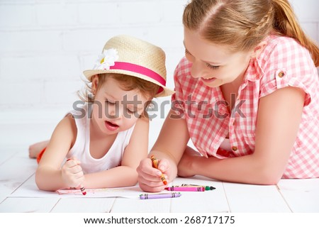 mother and baby daughter together paint a kid pencils - stock photo