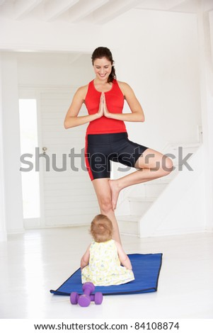 Mother and baby doing yoga - stock photo