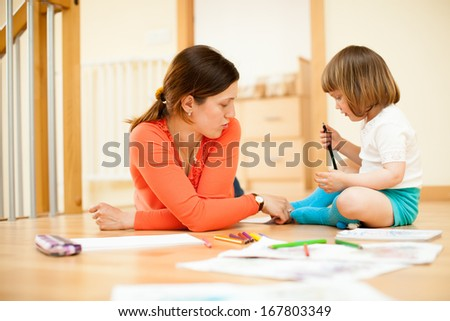 mother and baby drawing on parquet floor - stock photo