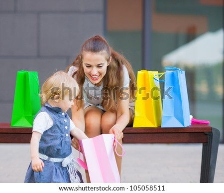 Mother and baby examines purchases after shopping - stock photo