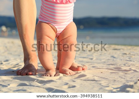 mother and baby feet on summer beach