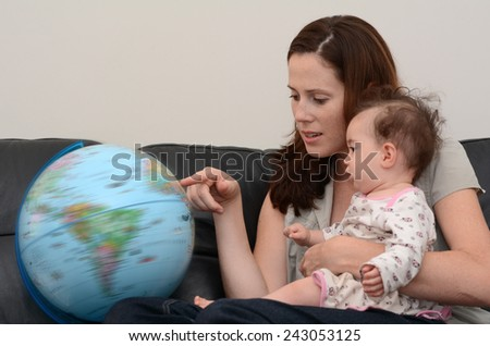 Mother and baby (girl age 06 months) search and examining the Globe  at home. Concept photo travel and education - stock photo