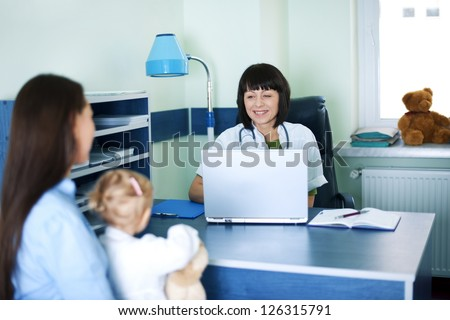 Mother and baby girl at doctors office - stock photo