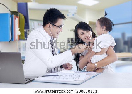 Mother and baby girl at the doctors office - stock photo