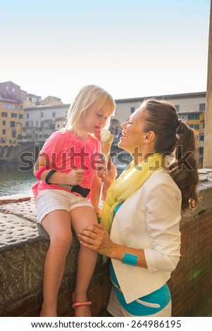 Mother and baby girl eating ice cream near ponte vecchio in florence, italy - stock photo