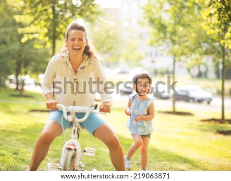 Mother and baby girl having fun with bicycle in park - stock photo