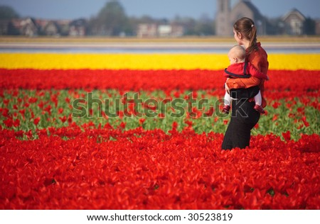 Mother and baby girl in red tulips field - stock photo