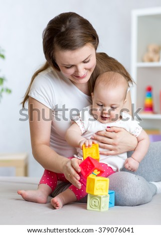 Mother and baby girl playing with developmental toys in living room - stock photo