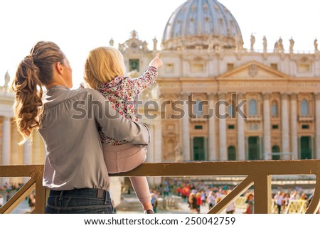 Mother and baby girl pointing on basilica di san pietro in vatican city state. rear view - stock photo