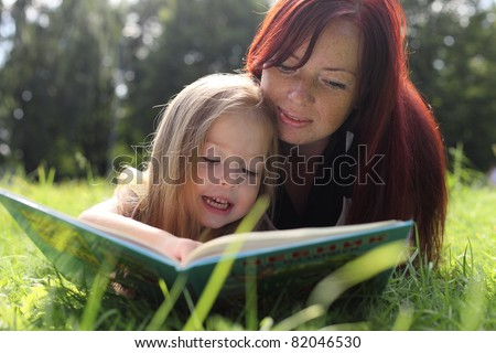 Mother and baby girl reading book - stock photo