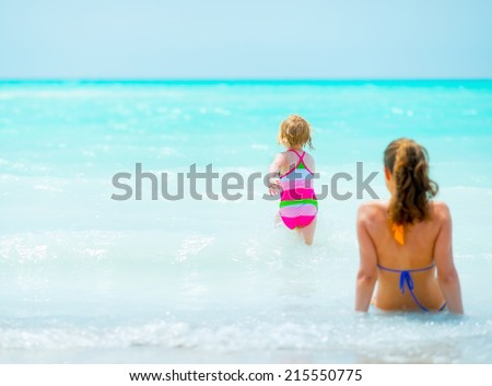 Mother and baby girl relaxing at seaside. rear view - stock photo