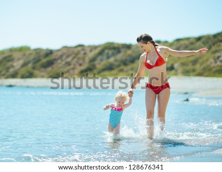 Mother and baby girl running on sea coast - stock photo