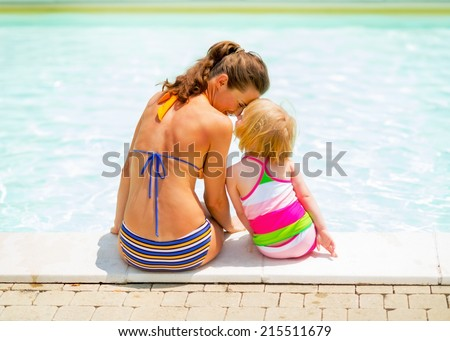 Mother and baby girl sitting near swimming pool. rear view - stock photo