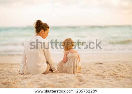 Mother and baby girl sitting on beach at the evening. rear view - stock photo
