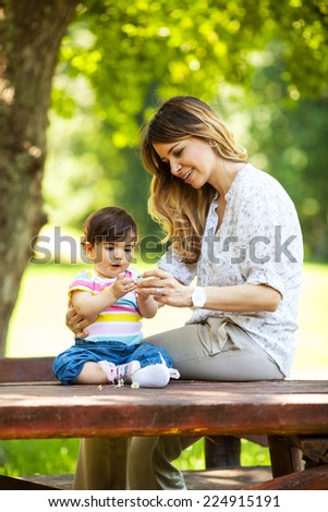 Mother and baby girl sitting on bench  at the park. - stock photo