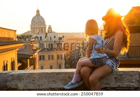 Mother and baby girl sitting on street overlooking rooftops of rome on sunset looking into distance - stock photo