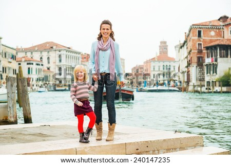 Mother and baby girl standing on embankment in venice, italy - stock photo