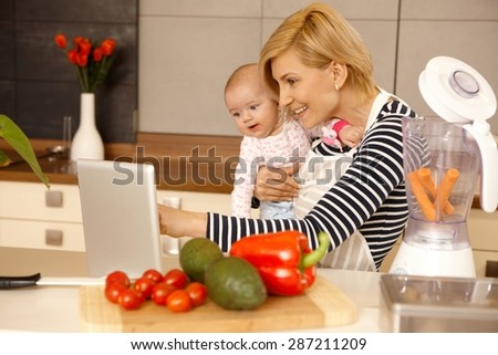 Mother and baby girl using laptop computer in kitchen, cooking. - stock photo
