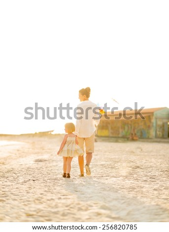 Mother and baby girl walking on beach at the evening. rear view - stock photo