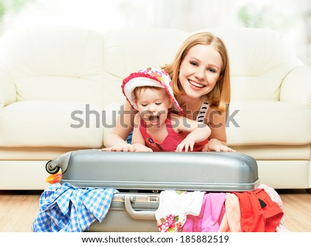 Mother and baby girl with suitcase baggage and clothes ready for traveling on vacation - stock photo