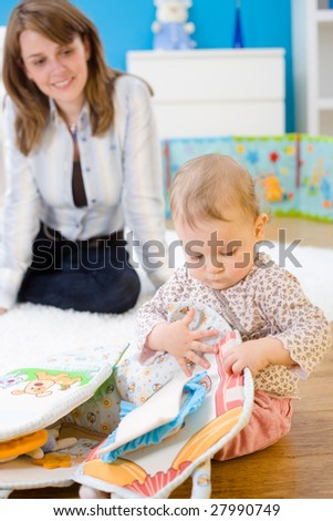Mother and baby girl (1 year old) playing on floor at home. - stock photo
