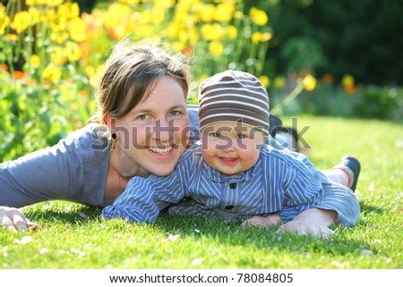 Mother and baby having fun in the garden - stock photo