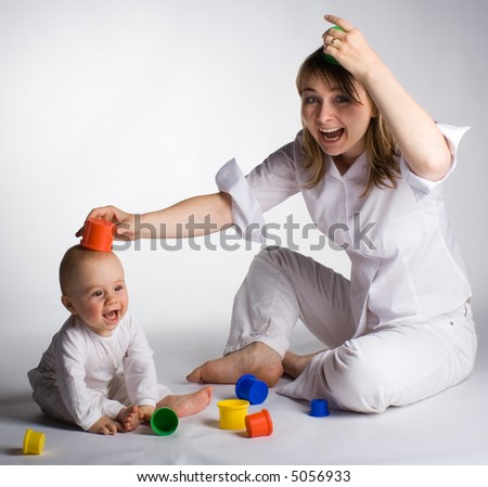 Mother and baby having fun with colorful toys - stock photo