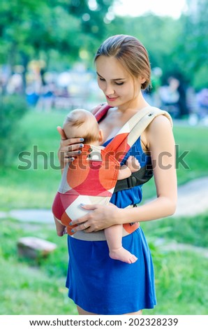 Mother and baby in backpack. Outdoor - stock photo