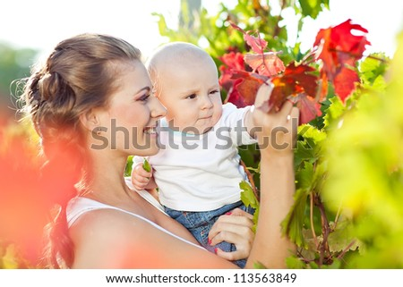 Mother and baby in park portrait - stock photo