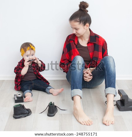 Mother and baby in red checkered shirts and jeans - stock photo