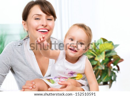Mother and Baby kissing and hugging at Home. Happy Smiling Family Portrait