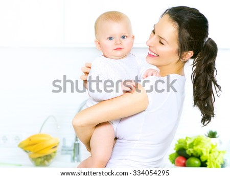 Mother and Baby kissing and hugging at Home. Happy Smiling Family Portrait. Happy Family. Mom and Her Child Having Fun together in the kitchen, diet,dieting concept. Healthy eating - stock photo