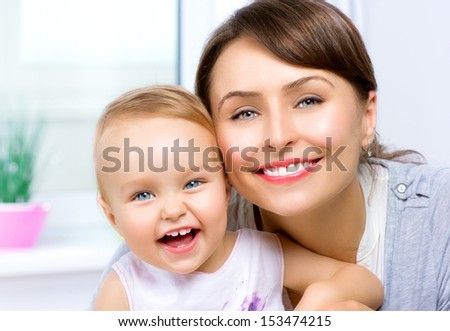 Mother and Baby kissing and hugging at Home. Happy Smiling Family Portrait. Mom and her Child Portrait - stock photo