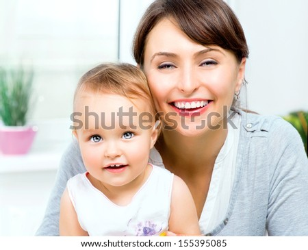 Mother and Baby kissing and hugging at Home. Happy Smiling Family Portrait. Mom and Her Child Having Fun together