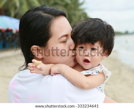 Mother and Baby kissing and hugging. Happy Family on the beach - stock photo