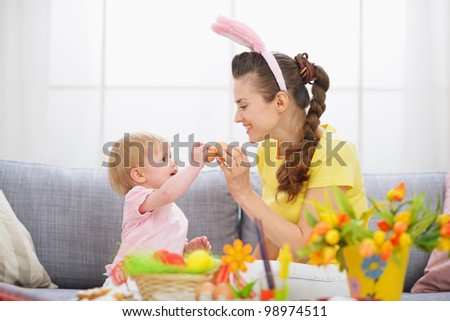Mother and baby knocking Easter eggs - stock photo