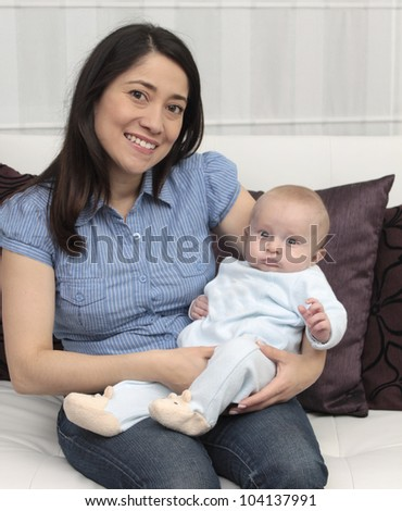 Mother and baby laugh together at home - stock photo