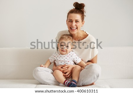 Mother and baby laugh together at home. They are sitting on the sofe in a brightly lit living room at the weekend together, lazy morning, warm and cozy scene. Selective focus - stock photo