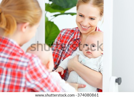 mother and baby look in the mirror and smile at home - stock photo