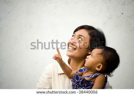 Mother and baby look up and pointing - stock photo