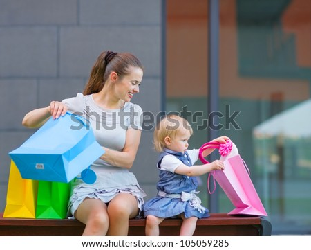Mother and baby looking into shopping bag - stock photo