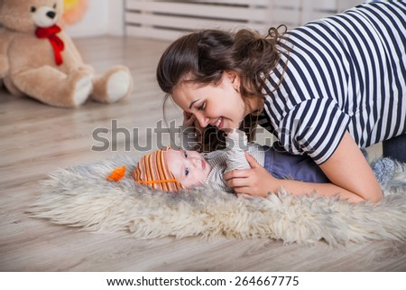 mother and baby lying on the floor - stock photo