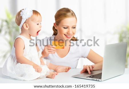 mother and baby make purchases over the Internet with a laptop and a credit card - stock photo