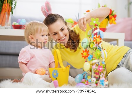 Mother and baby making Easter decoration - stock photo