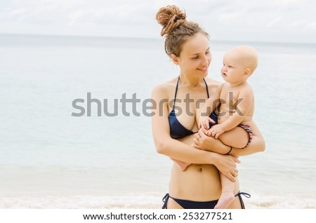 Mother and baby on the coastline - stock photo