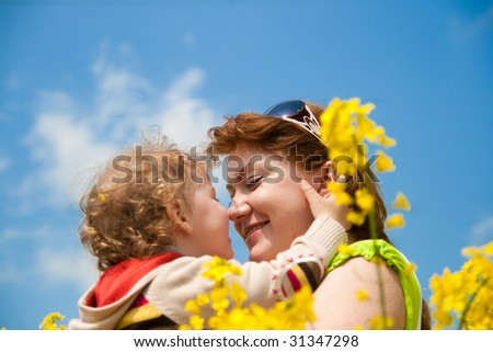 mother and baby on the rapeseed field - stock photo