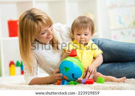 mother and baby play with wooden toy - stock photo