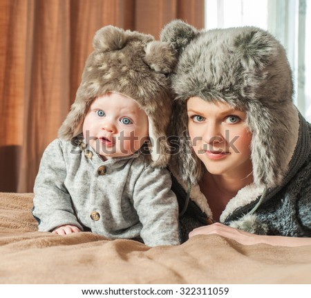 Mother and baby playing and smiling. Happy family.Home interior. Winter season. - stock photo