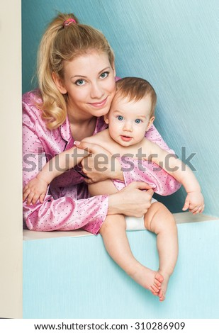 Mother and baby playing and smiling. Happy family. The home interior. - stock photo